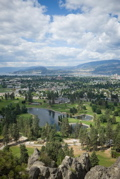 Image: city of Kelowna with golf course in foreground, lake & mountain in background.